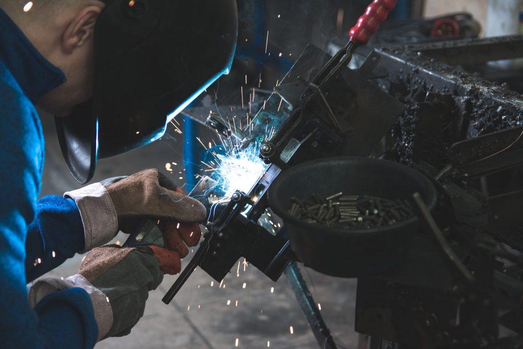 Ouvrier en train de réparer une machine industrielle