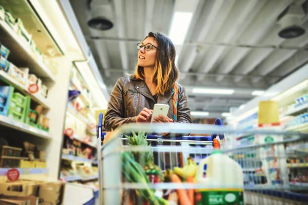 Jeune femme dans un supermarché avec son téléphone