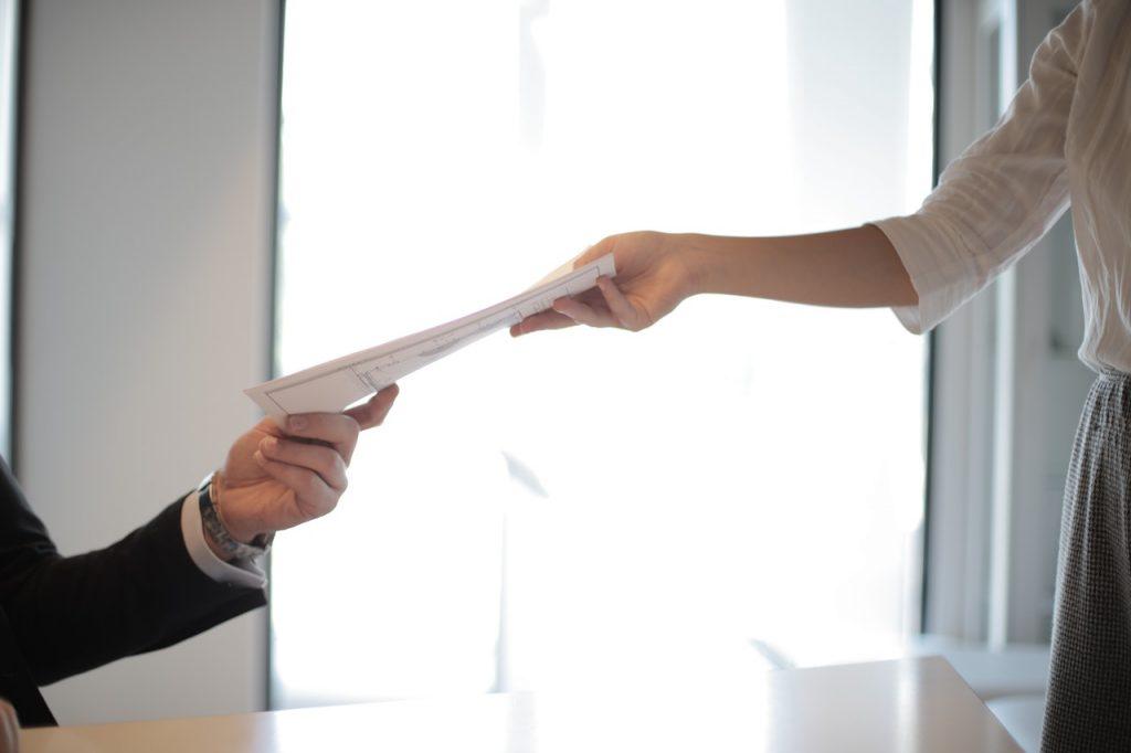 personne qui tend un document à une autre personne